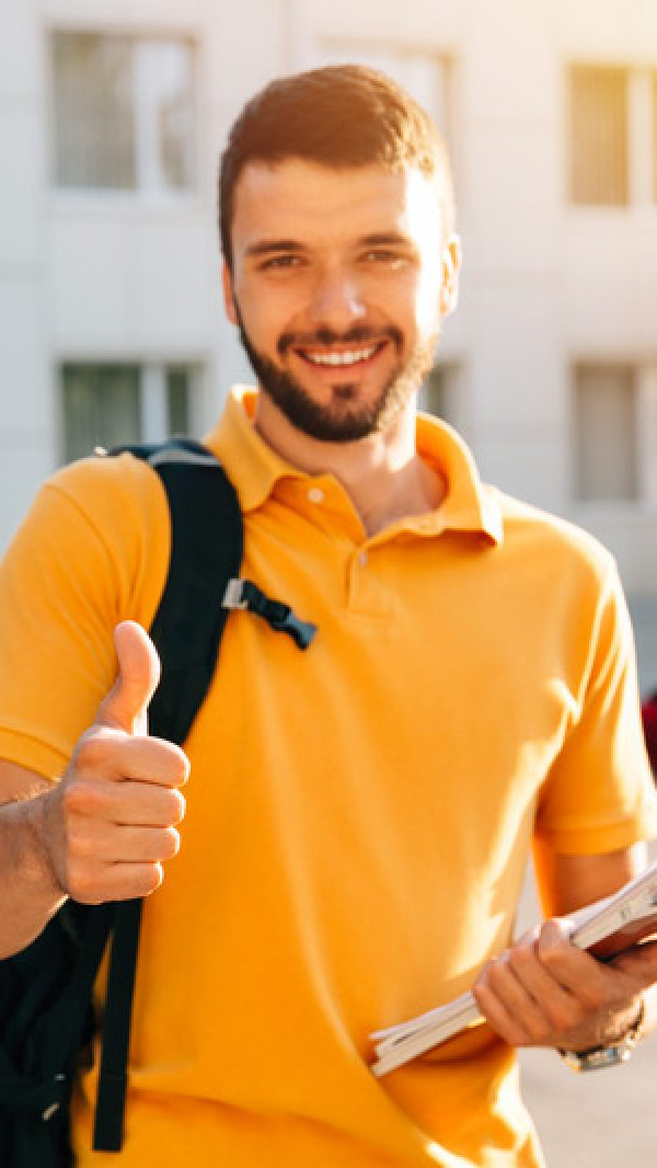 Young attractive smiling student showing thumb up outdoors on campus at the university. Selective focus
